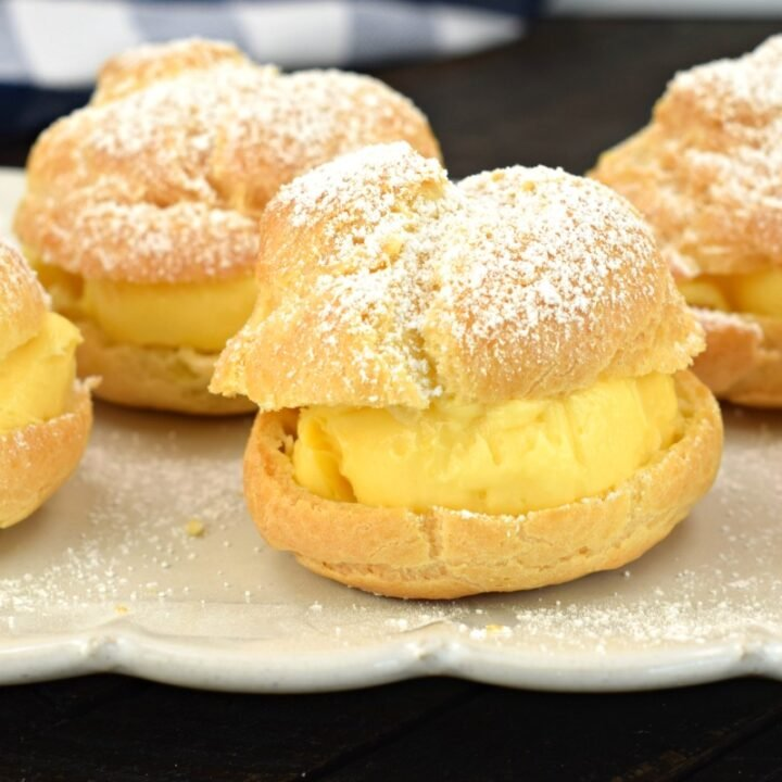 Cream puffs with vanilla custard filling and topped with powdered sugar on a white serving plate.