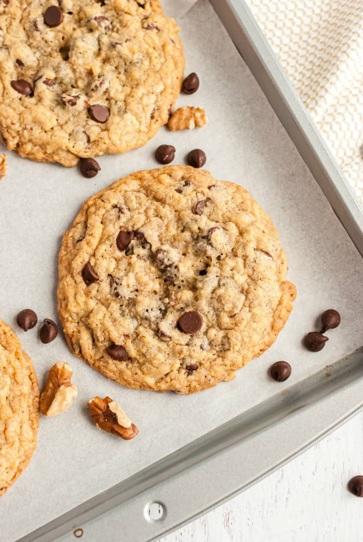 Large chocolate chip cookies baked on a piece of parchment paper lined cookie sheet.
