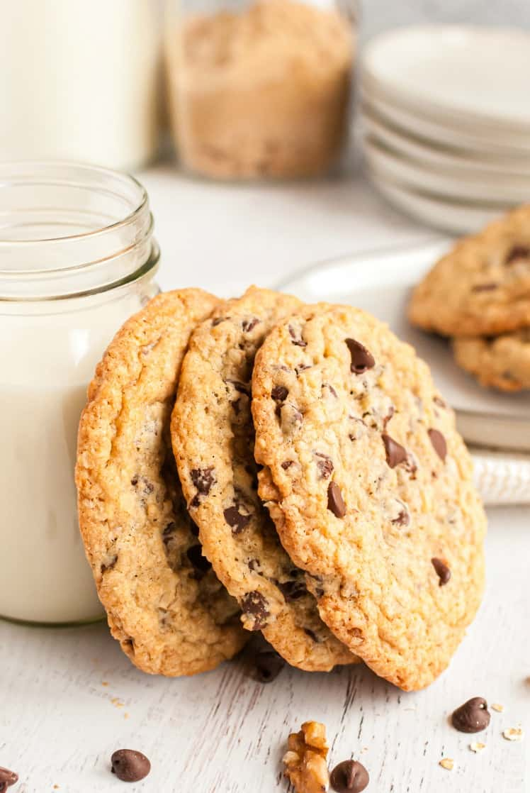 Three large chocolate chip cookies stacked vertically against a clear mug of milk.