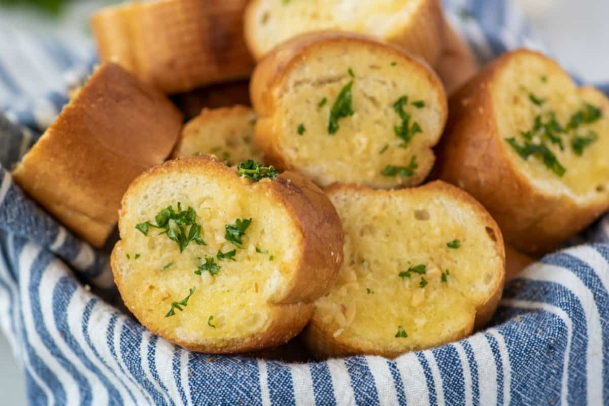 Garlic bread slices in a bowl with a blue and white striped linen napkin.