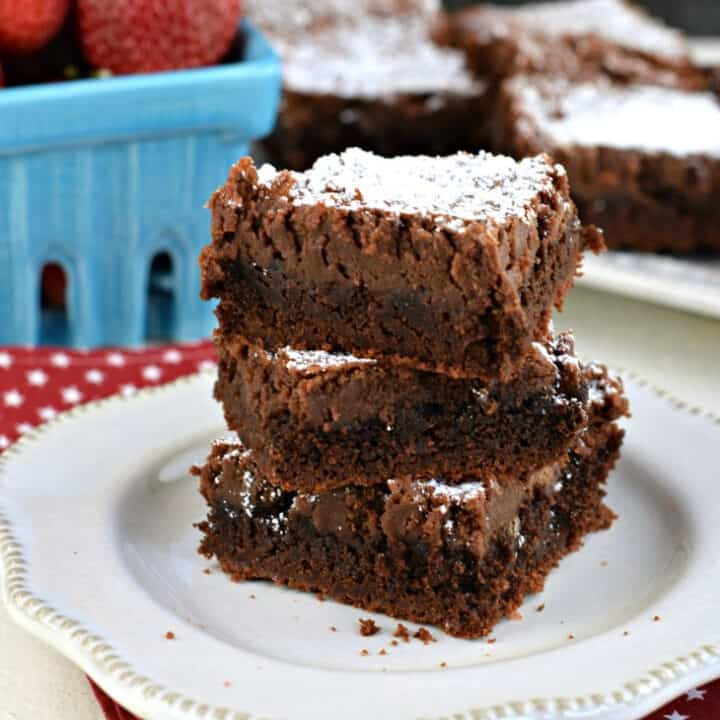Gooey brownie bars stacked on a white plate.