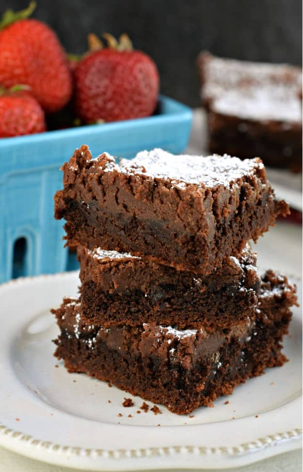 Stack of three gooey chocolate brownie bars sprinkled with powdered sugar on a white plate with red napkin.