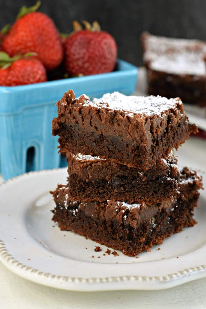 Three chocolate cake bars stacked up on a white plate with a bowl of strawberries.