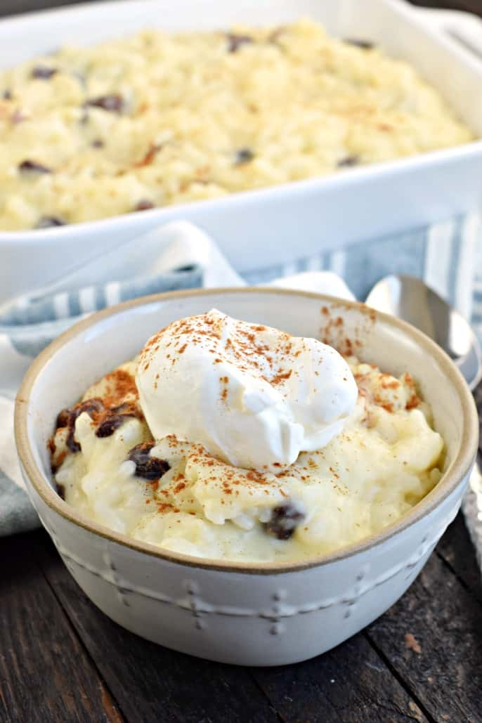 White bowl with rice pudding and whipped cream. Large white rectangle dish filled with rice pudding in background.