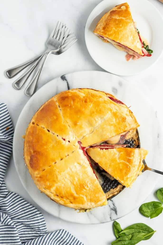 Whole sandwich torte filled with meat, cheese, spinach, and red peppers.
