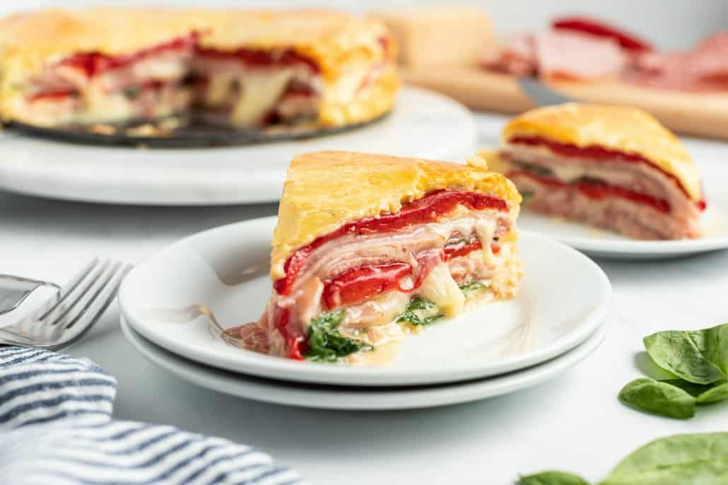 Slice of Italian sandwich torte on a stack of white plates, with cheese oozing out.