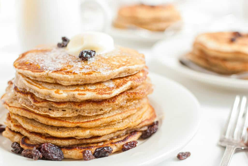 Stack of oatmeal cookie pancakes with butter, cinnamon, and raisins on a white plate.