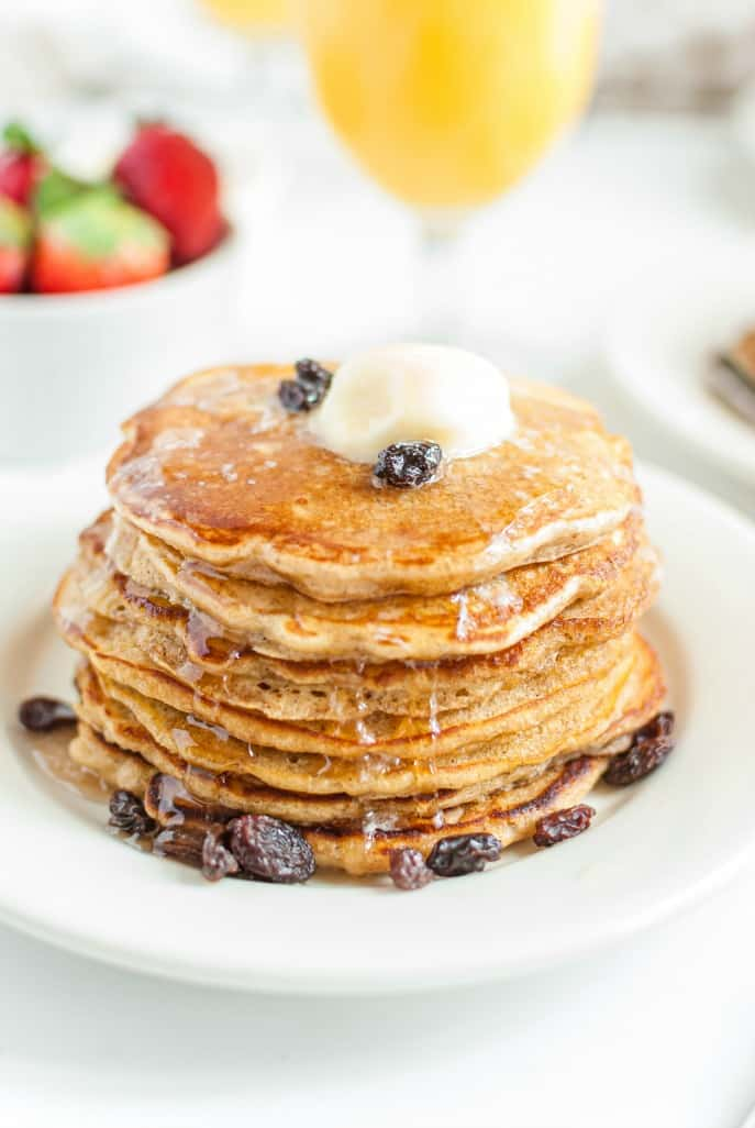 Stack of oatmeal pancakes topped with butter, cinnamon, and raisins!