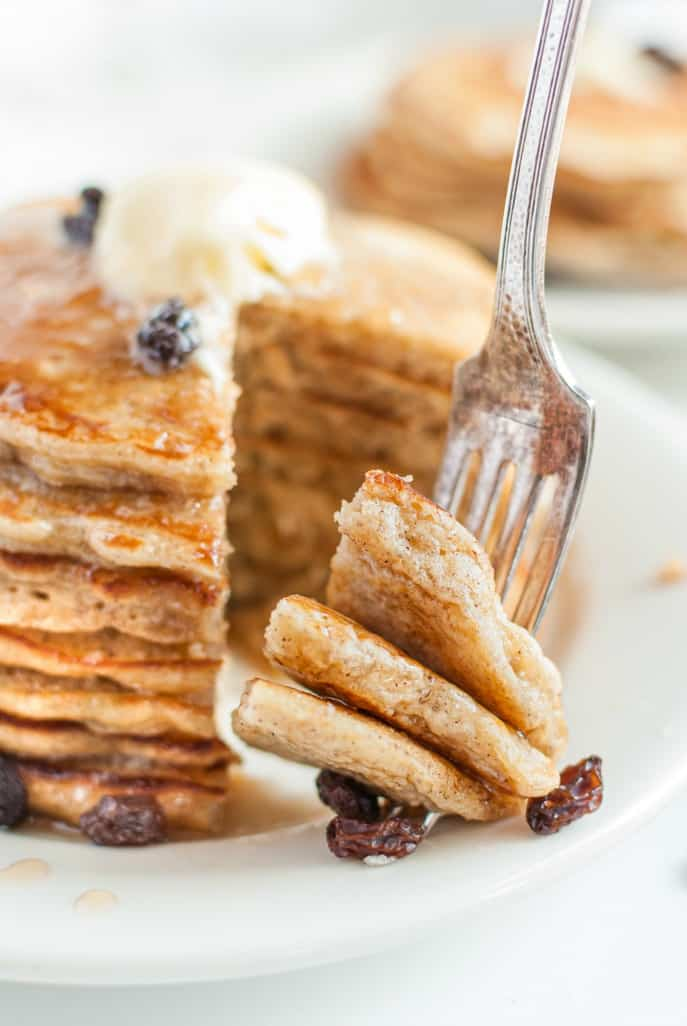 Stack of pancakes with one bite cut and being lifted by a fork. Raisins on the side.