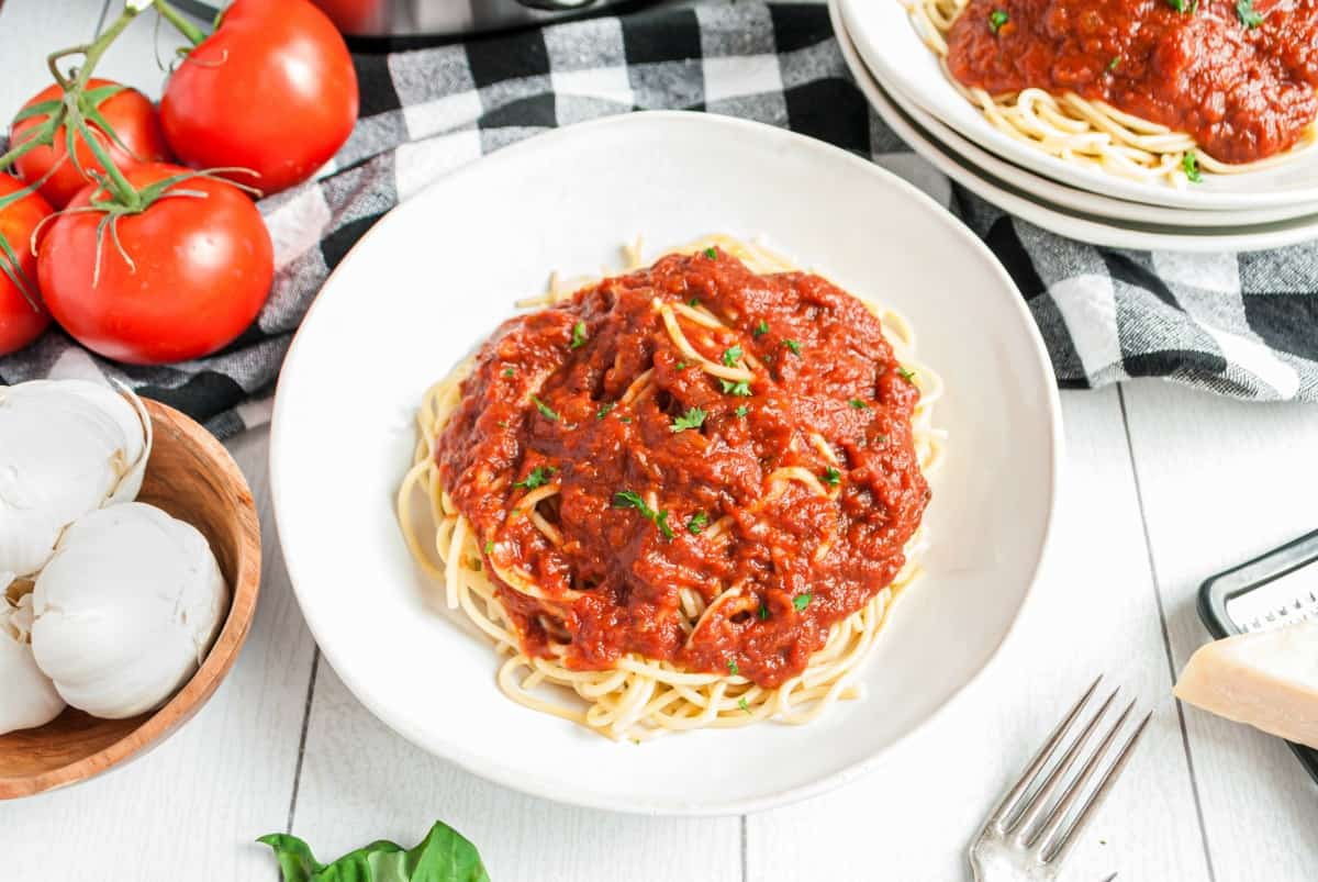 White pasta bowl with spaghetti and homemade marinara sauce. Served with a black and white napkin and fresh tomatoes on the side.