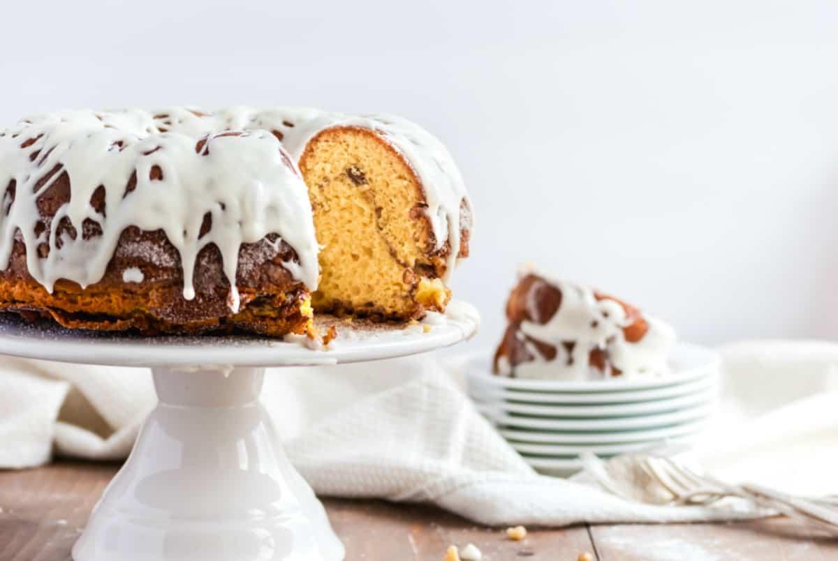 Bundt cake with vanilla glaze on a white cake platter.