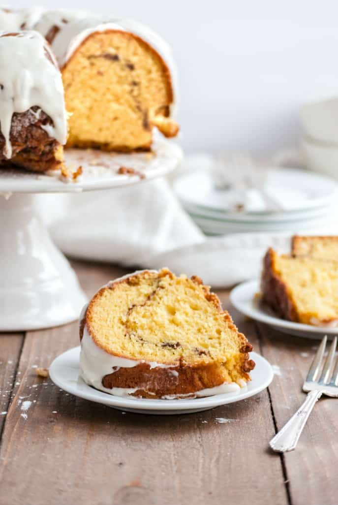 Slice of streusel filling bundt cake on a white plate with wooden table.