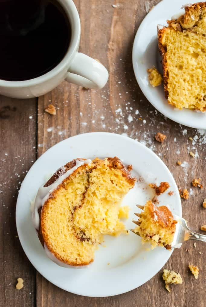 White plate with a slice of cinnamon bundt cake and cup of coffee in a white mug.