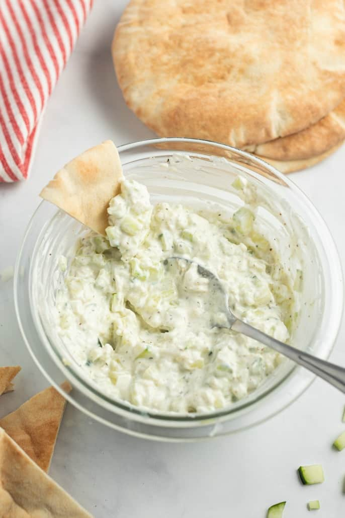 Clear glass bowl with homemade tzatziki sauce and pita bread.