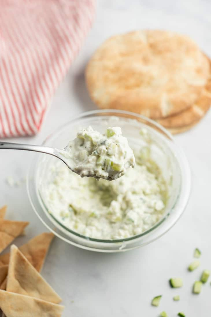 Clear glass bowl of tzatziki cucumber sauce with a metal spoon lifting a scoop out of the bowl.