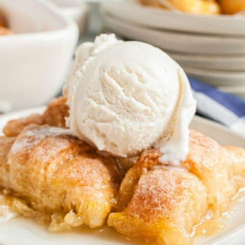 White dessert plate with several apple dumplings and a big scoop of vanilla ice cream on top.