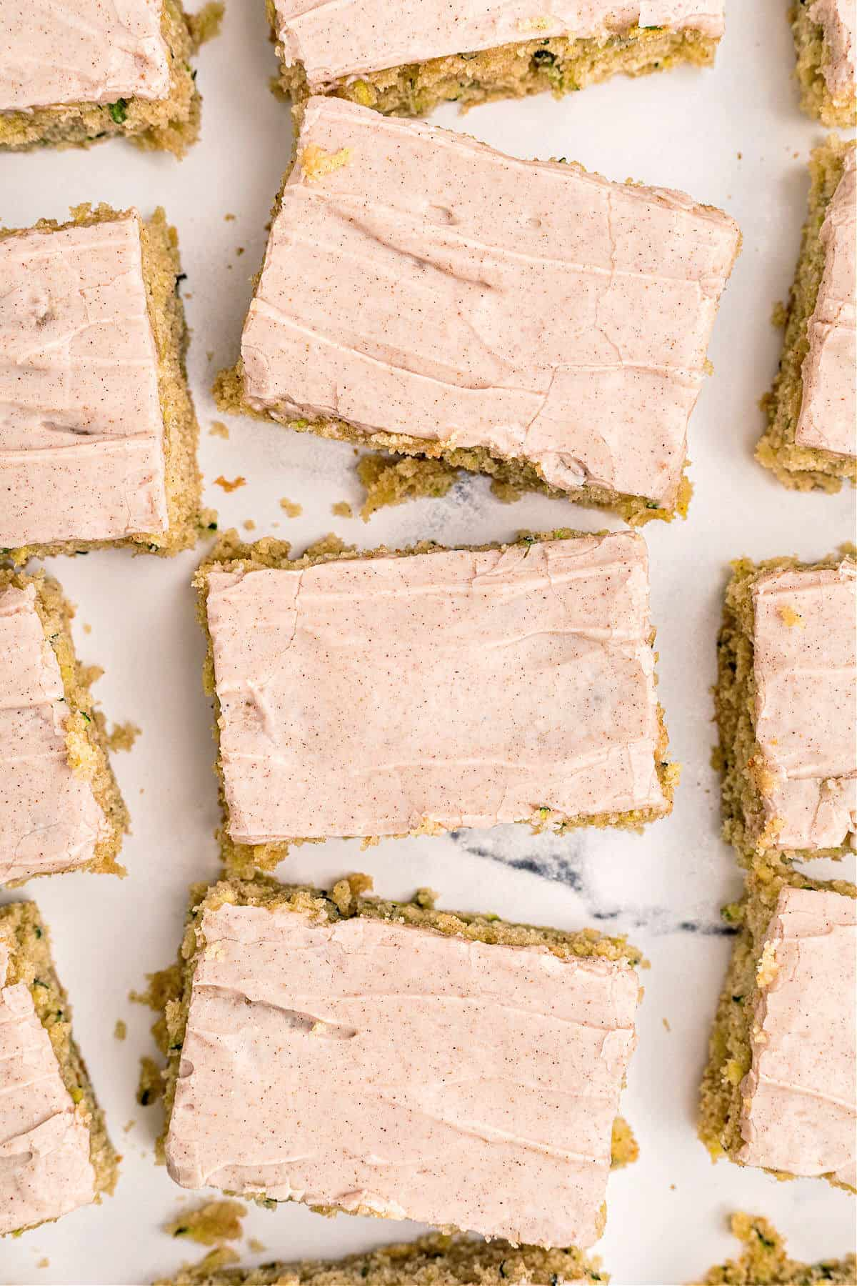 Cinnamon frosted zucchini bars cut into squares on white parchment paper.