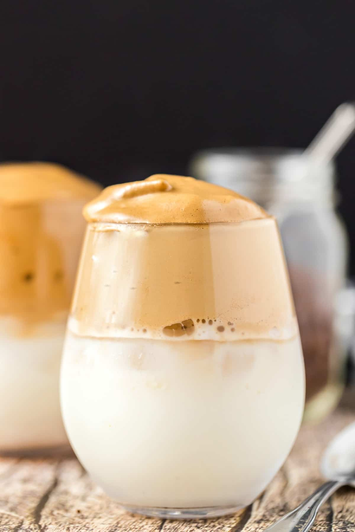 Clear stemless wine glass with whipped coffee over milk.