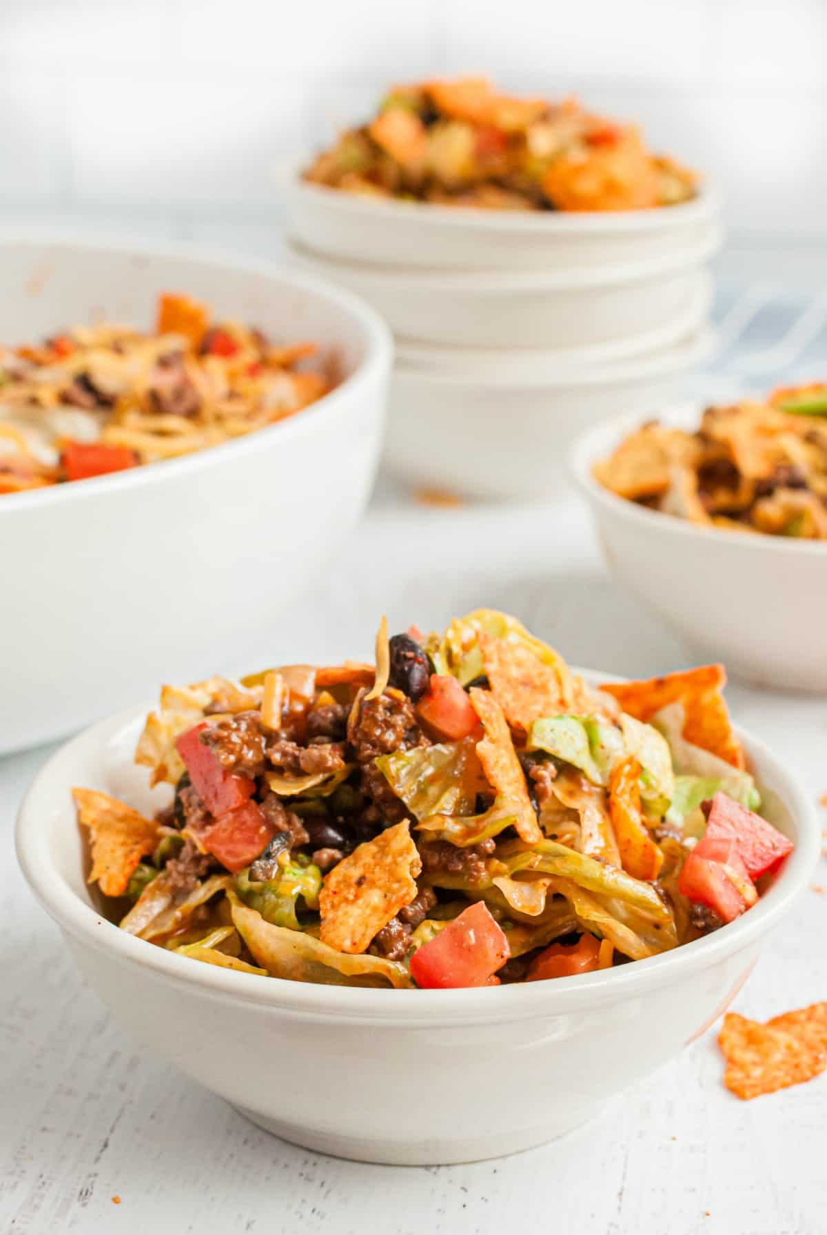 Taco salad in white dinner bowls topped with doritos.
