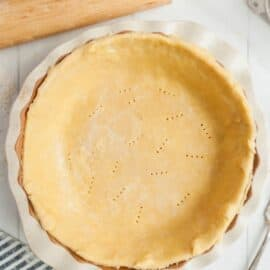 Homemade pie crust in a pie plate before baking with a rolling pin in background.