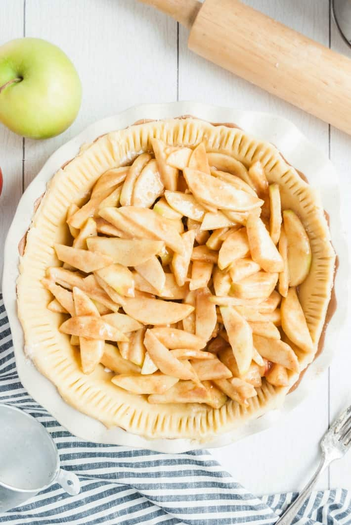 Pie crust in a pie plate filled with apple slices before baking.