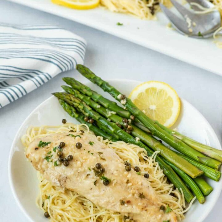 Chicken piccata on a white dinner plate with pasta noodles, grilled asparagus, and a slice of lemon.