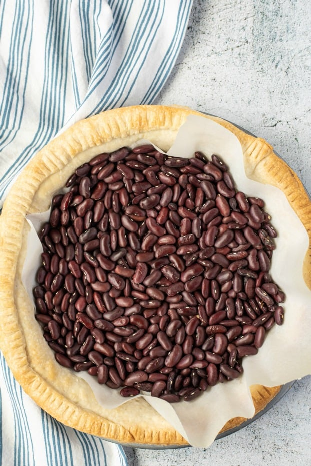 Baked pie crust with parchment paper and beans to show how to prebake a pie crust.