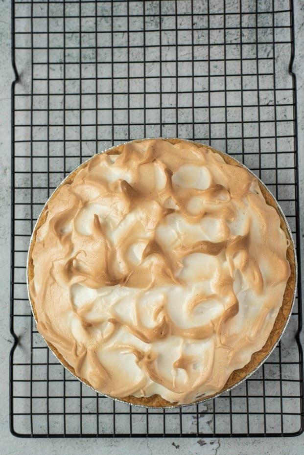 Baked lemon meringue pie on a wire rack to cool.