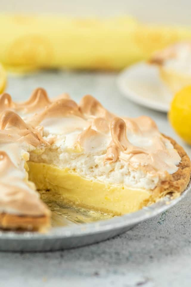 Lemon meringue pie in a metal pie plate with one slice removed.