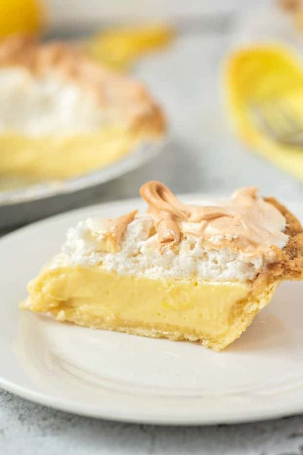Slice of lemon meringue pie on a white plate.