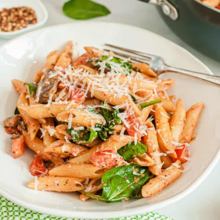 Penne pasta in a white bowl with tomato cream sauce, spinach, tomatoes, and mushrooms.