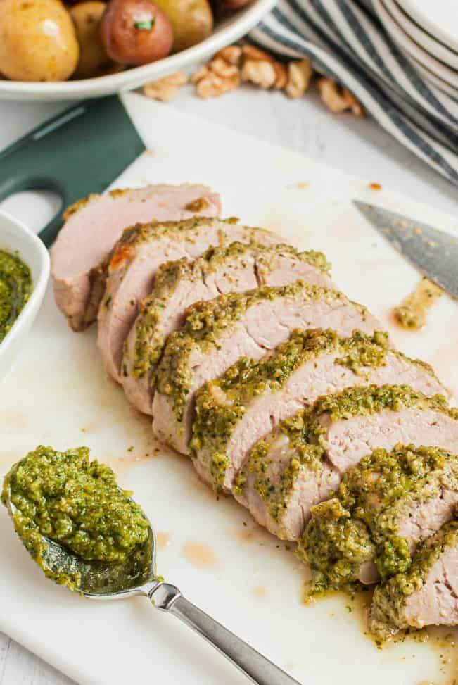 Thick walnut pesto glazed on top of a sliced pork tenderloin after cooking and ready to serve.