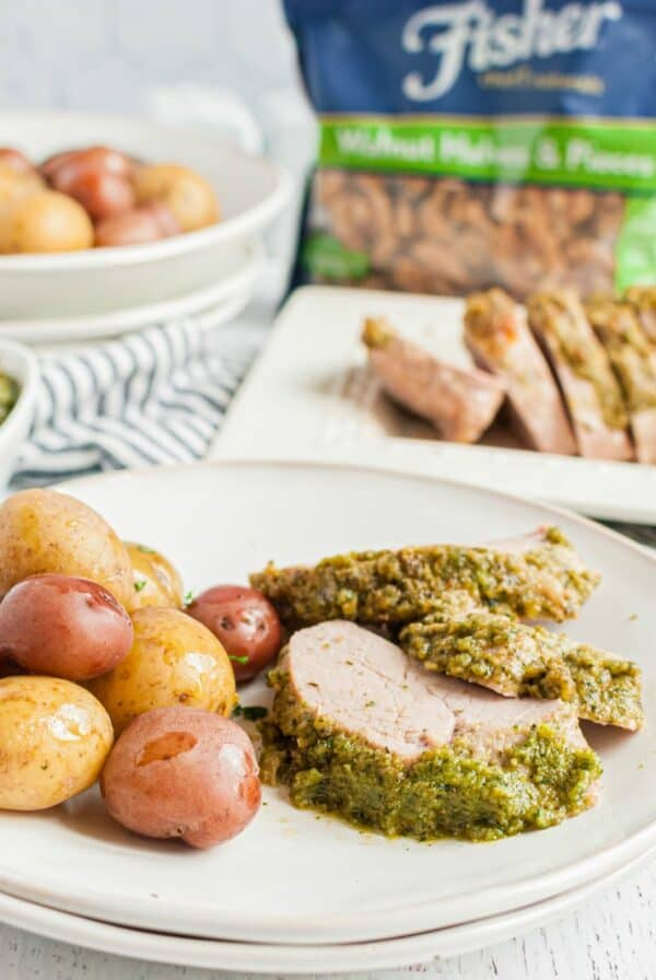 White dinner plate with sliced pesto topped pork tenderloin and baby potatoes, with a bag of Fisher Nuts walnuts in the background.