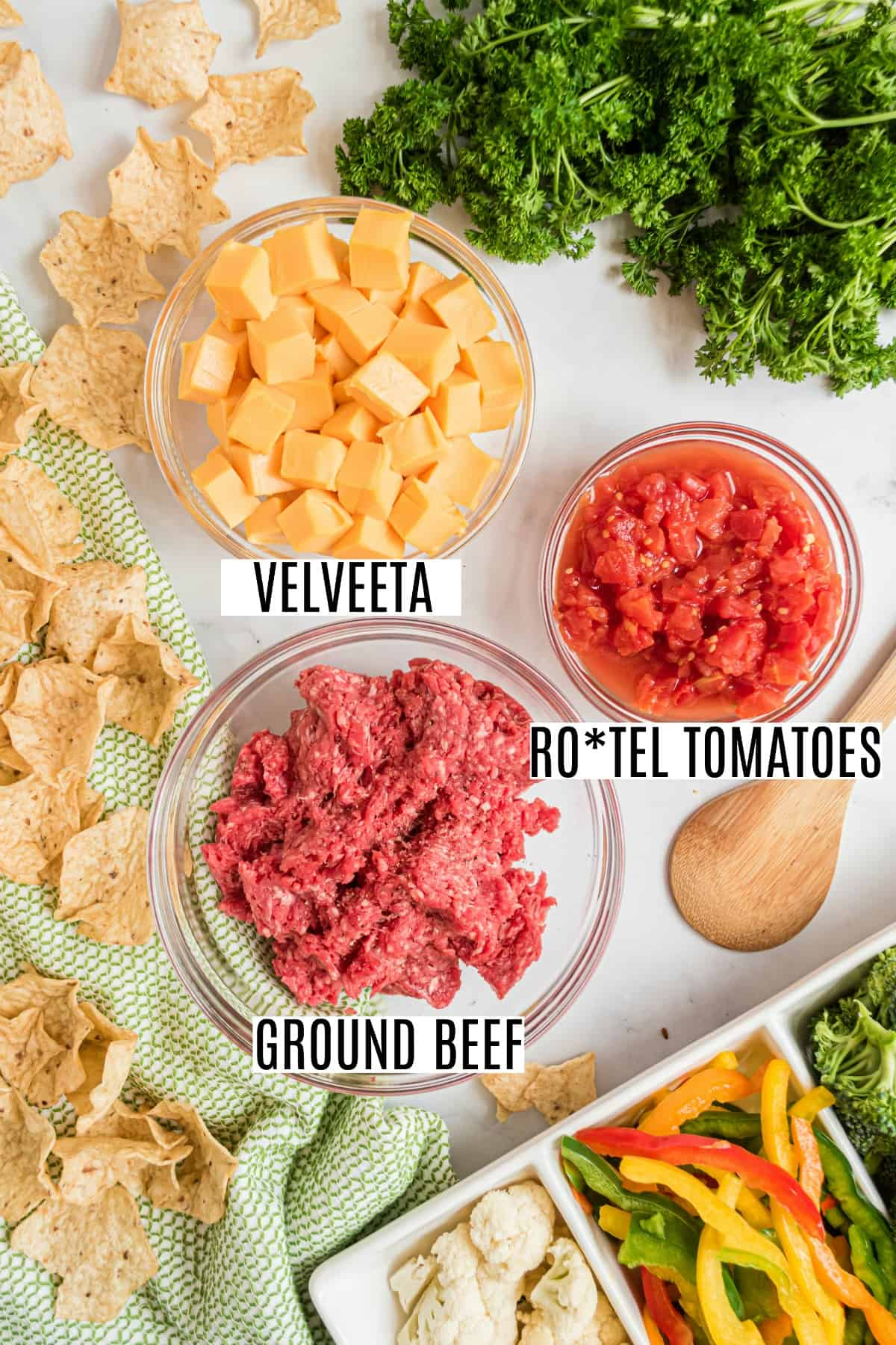 Three ingredients needed to make rotel dip, including ground beef, velveeta cheese, and rotel tomatoes.