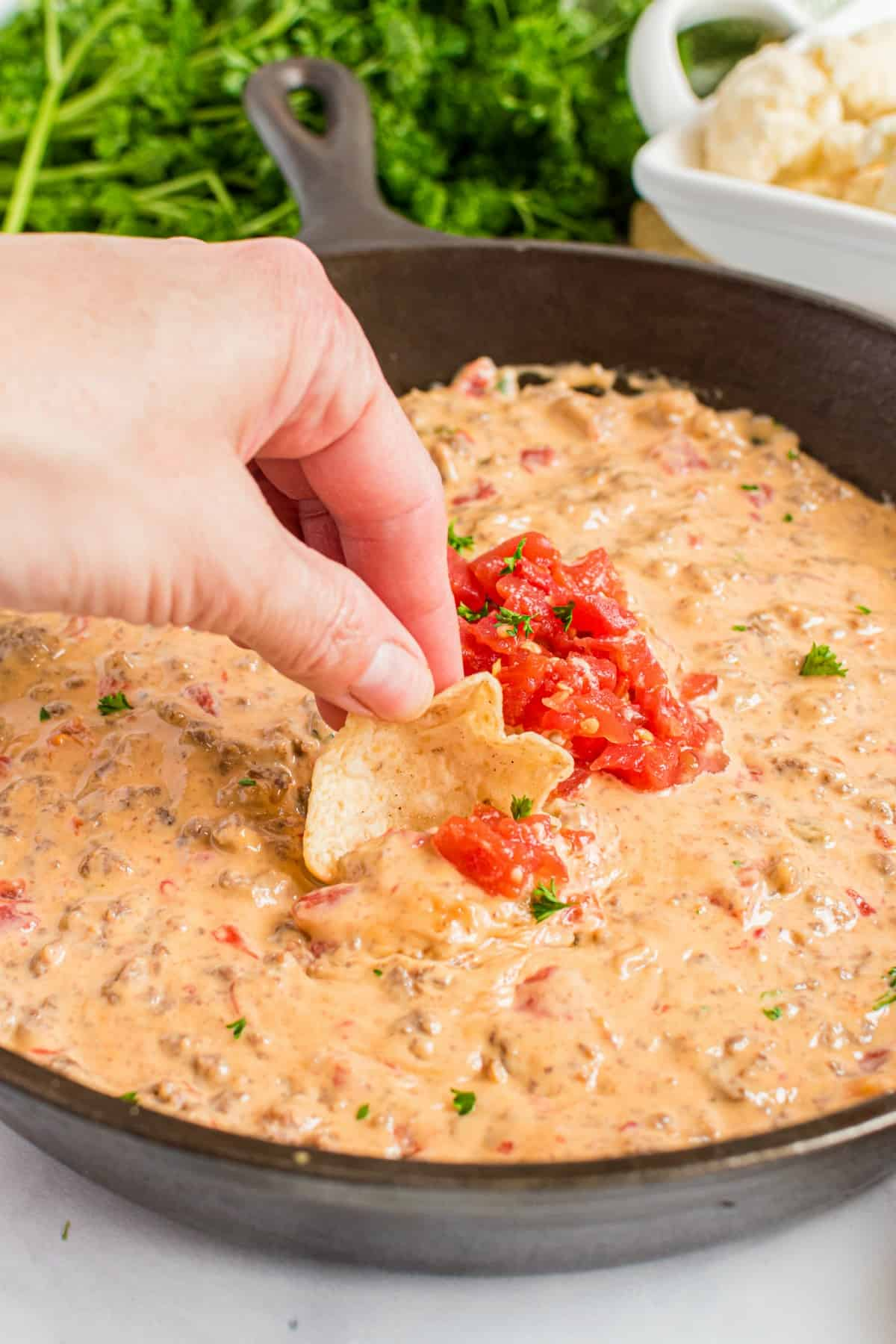 Cheesy rotel dip in a black cast iron skillet with a hand scooping dip on a tortilla chip.