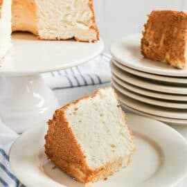 Angel food cake on a white cake platter with large wedges cut on white dessert plates.