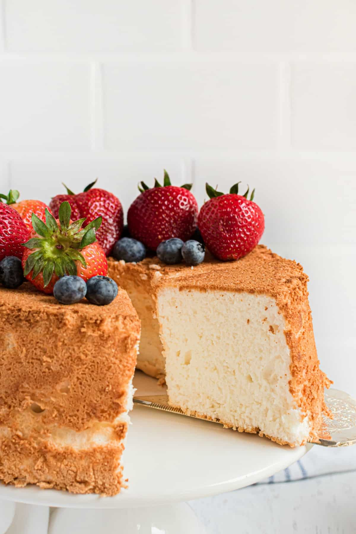 Angel food cake on a white cake platter topped with fresh berries. One slice removed.