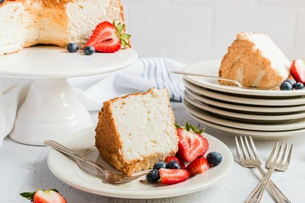 Angel food cake sliced and served on white cake plates with fresh cut berries.