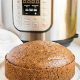 Banana Bread on a white plate with instant pot in background.
