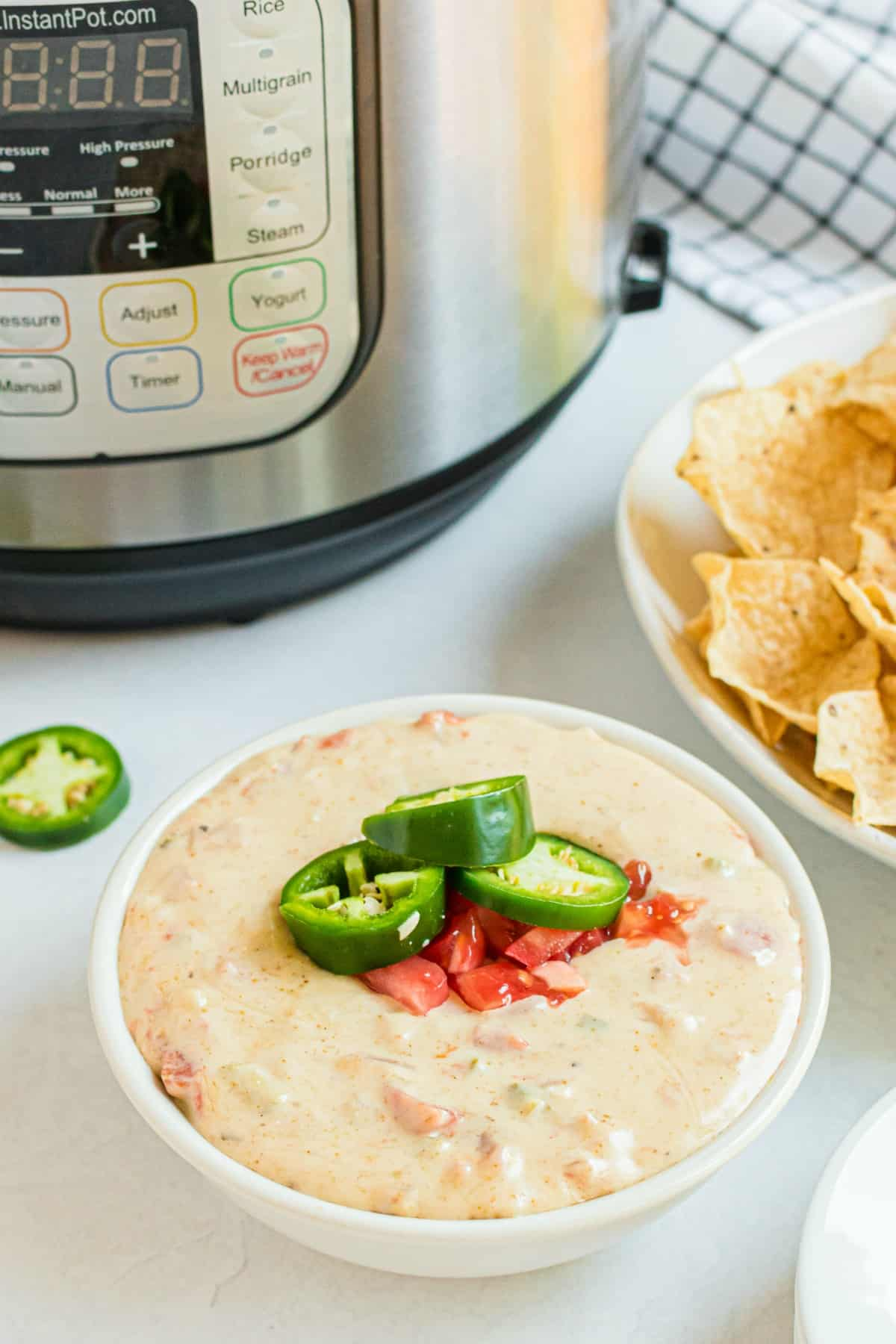 Queso in a white bowl with instant pot in background. Garnished with rotel tomatoes and jalapenos.