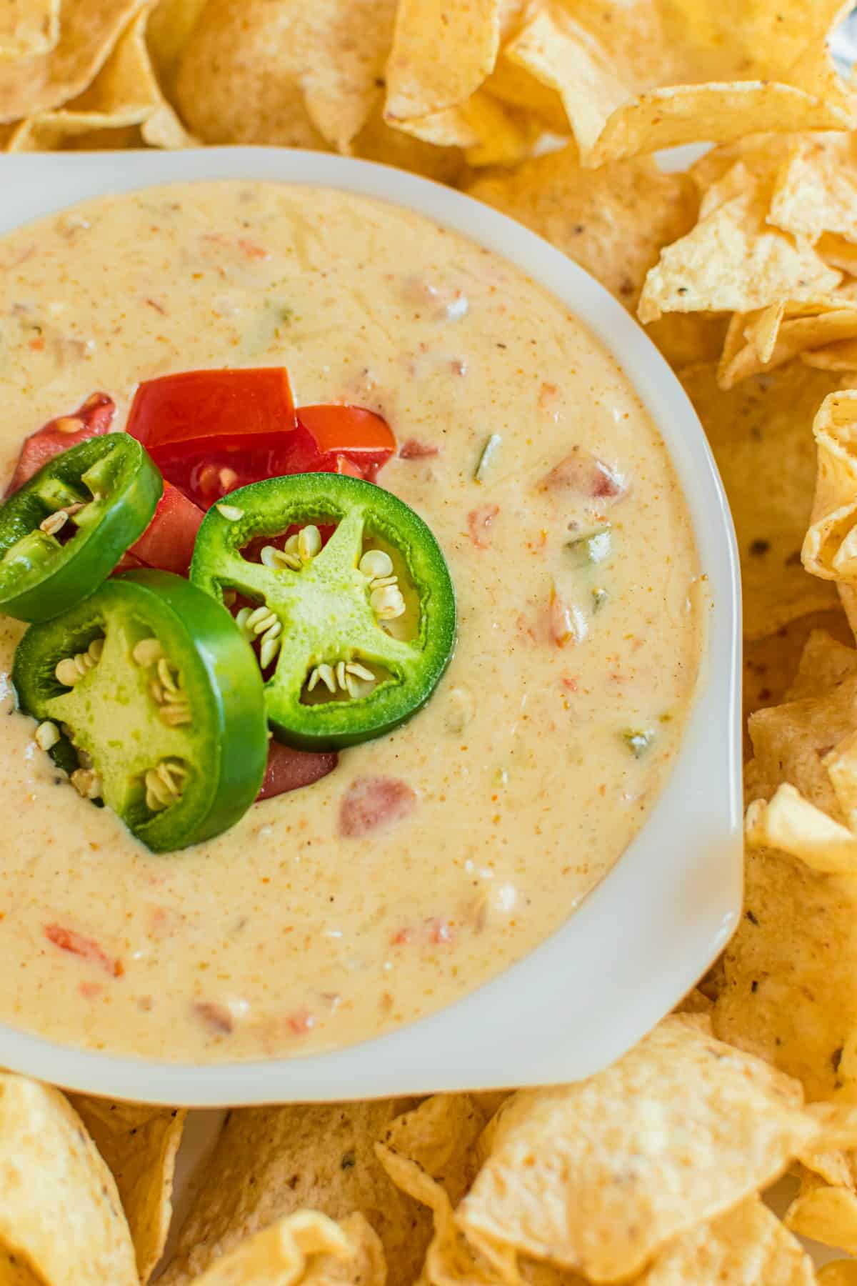 Platter of tortilla chips with a white bowl of queso in the middle. Garnish of jalapeno and rotel tomatoes on the queso.
