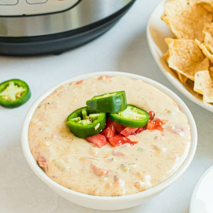 Queso in a white bowl with instant pot in background. Served with tortilla chips.