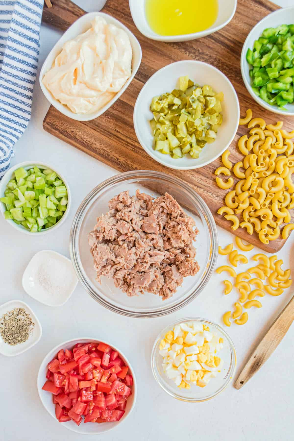 Ingredients for macaroni salad including tuna, vegetables, pickles, eggs and creamy dressing.