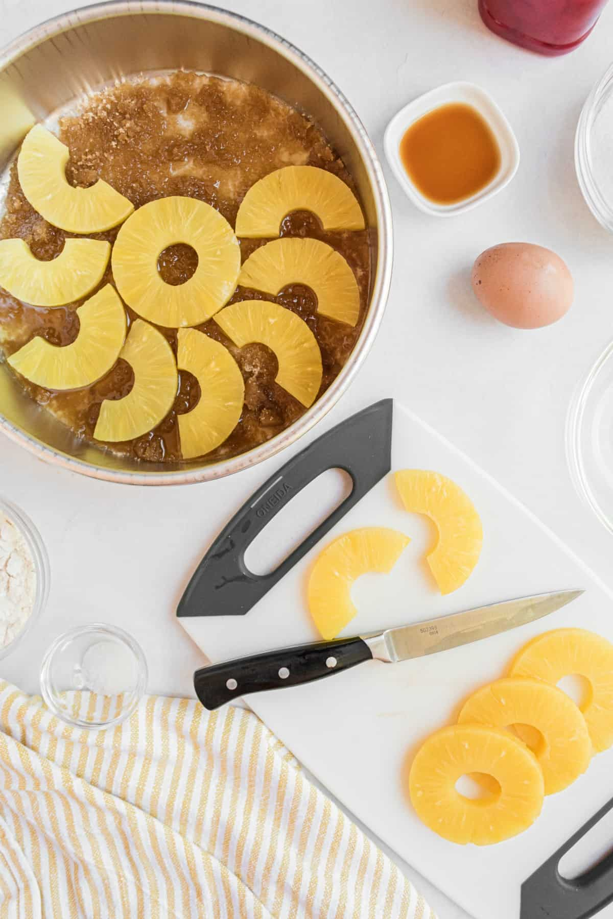 Pineapple slices being cut in half and arranged in the melted butter and brown sugar cake pan.