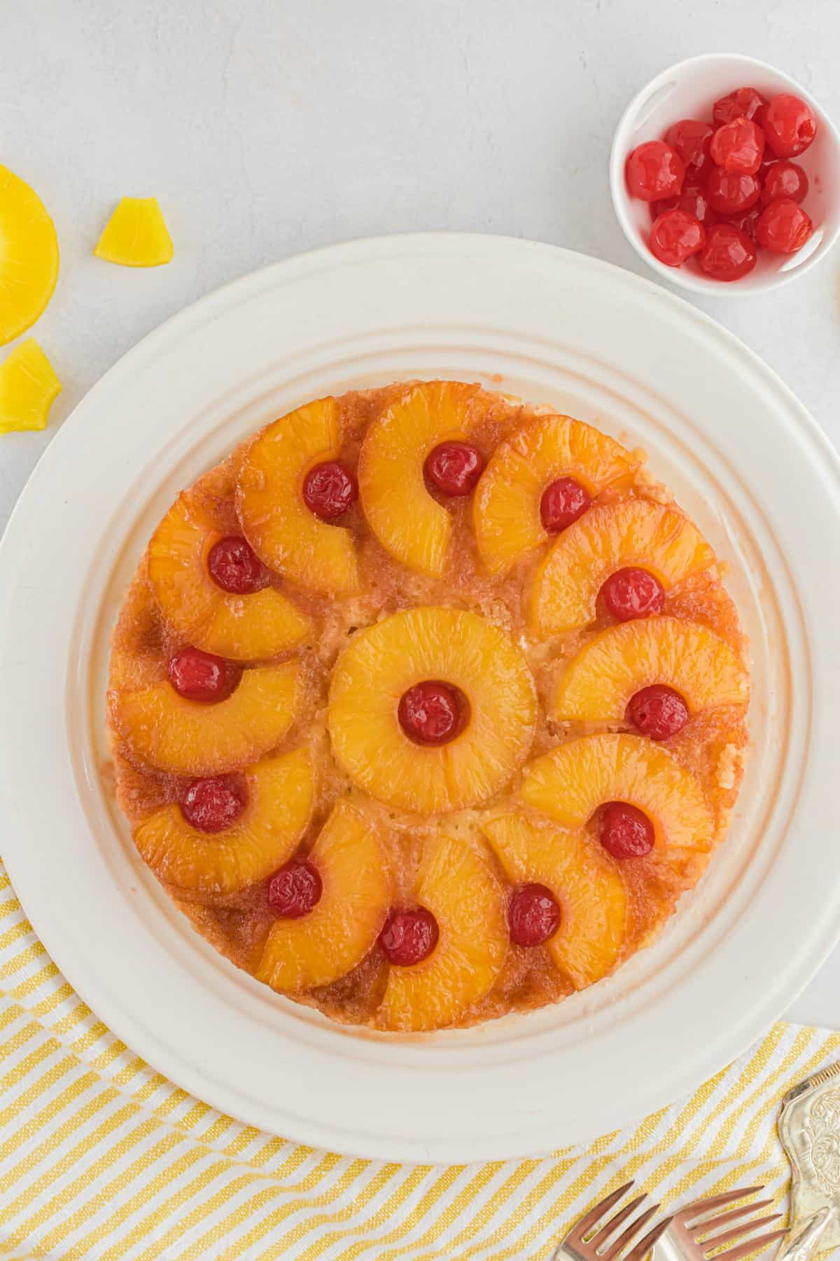 Pineapple upside down cake on a white cake platter with a small bowl of cherries in background.