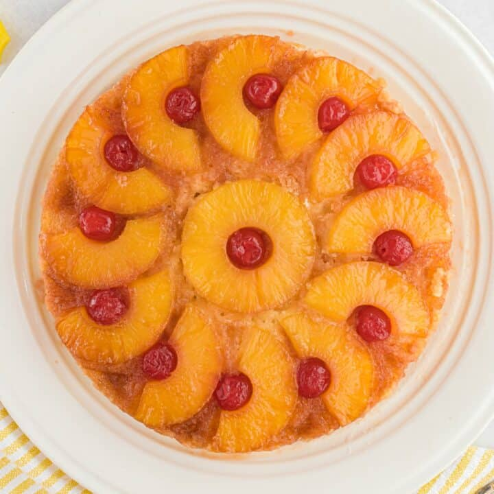 Pineapple upside down cake on a white cake plate.