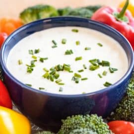 Dark blue bowl filled with homemade ranch dressing, topped with chives, and surrounded by fresh cut vegetables.
