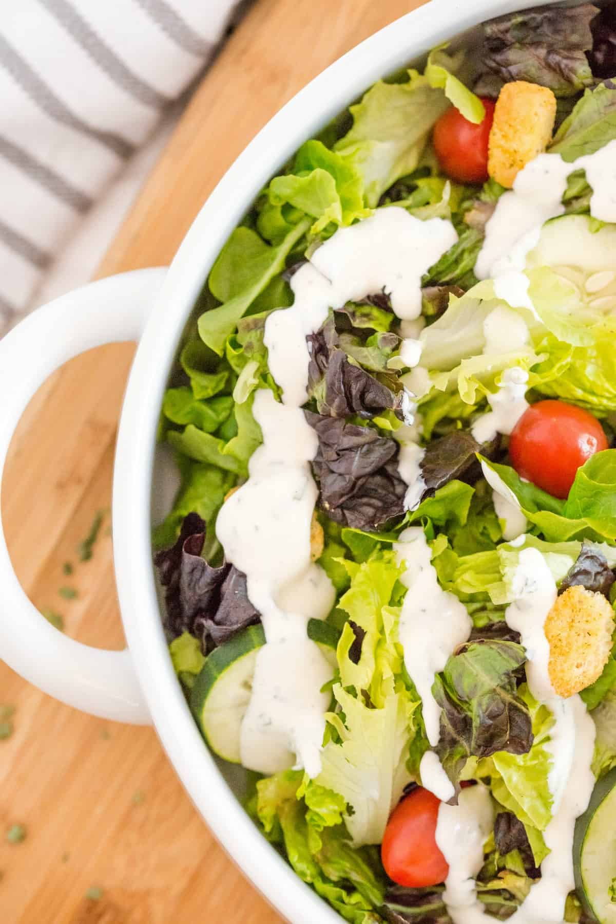 Leafy green salad in a white bowl topped with cherry tomatoes, croutons, and homemade ranch dressing.