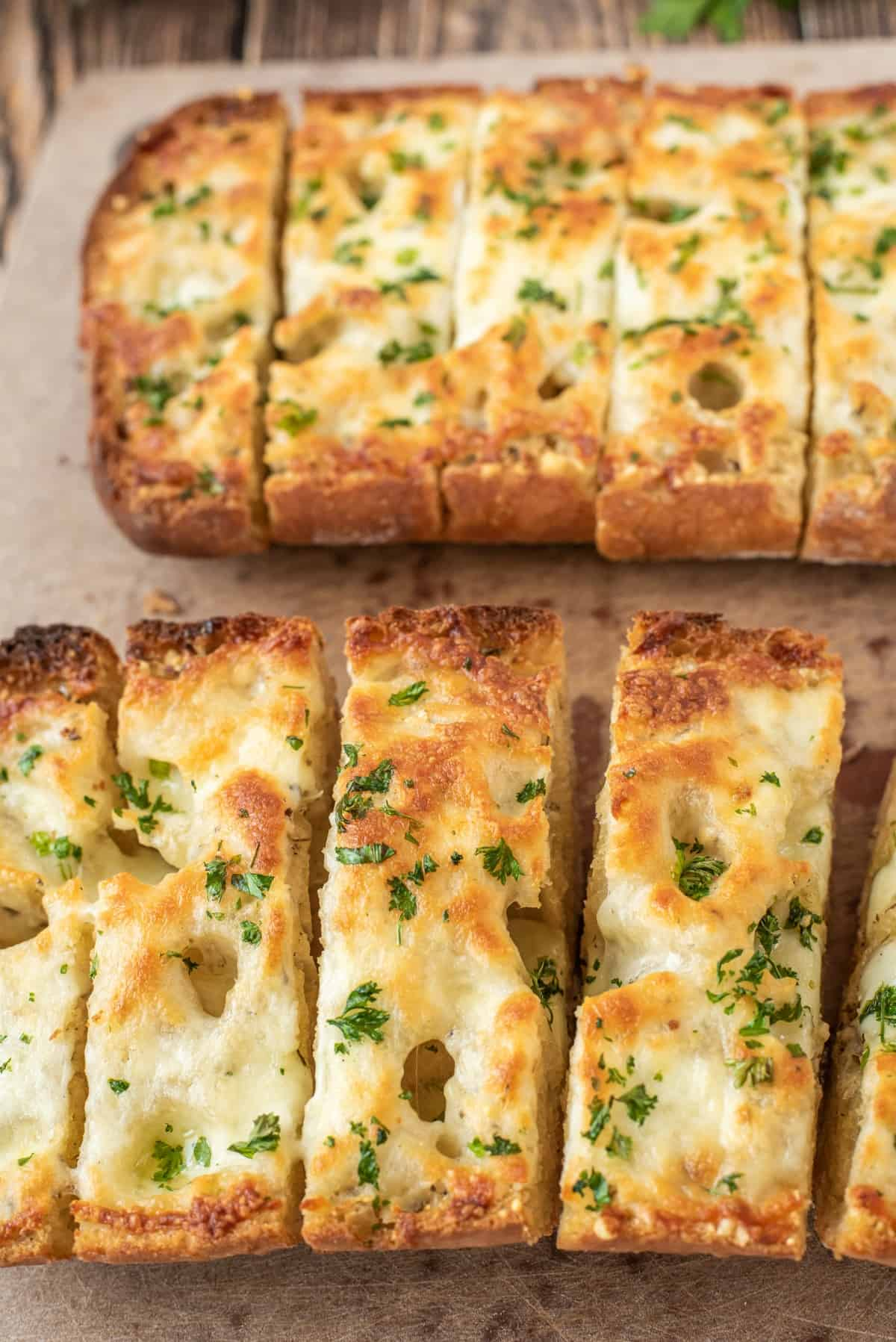 Cheesy garlic bread on parchment paper, sliced.