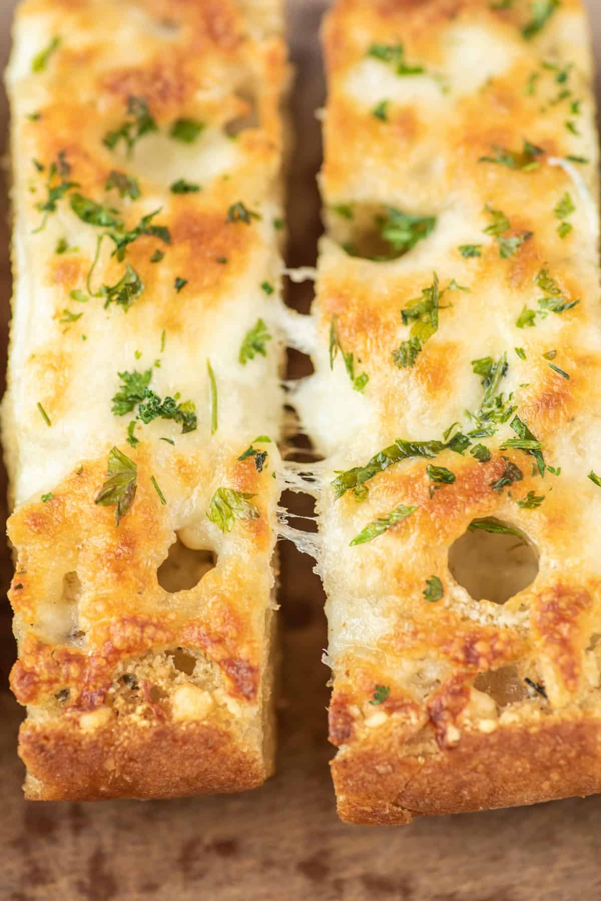 Cheesy garlic bread being pulled apart.